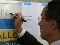 DC Mayor Vincent C. Gray signing school emblem - Ballou High School 'Topping Out' Ceremony