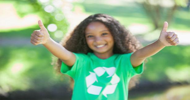 Girl wearing green recycle shirt with her thumbs up