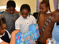 Seaton ES third graders demonstrate their functioning candy dispenser constructed from recyclable water jugs, cardboard boxes, and discarded paper.