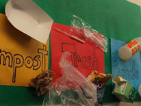 This sign, created by Deal students, hangs in Deal's school cafeteria to inform others about what materials should go in each different collection bin.